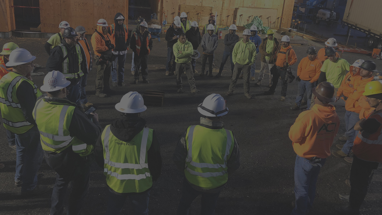 Accuset Construction crew holding safety meeting wearing hardhats and safety gear